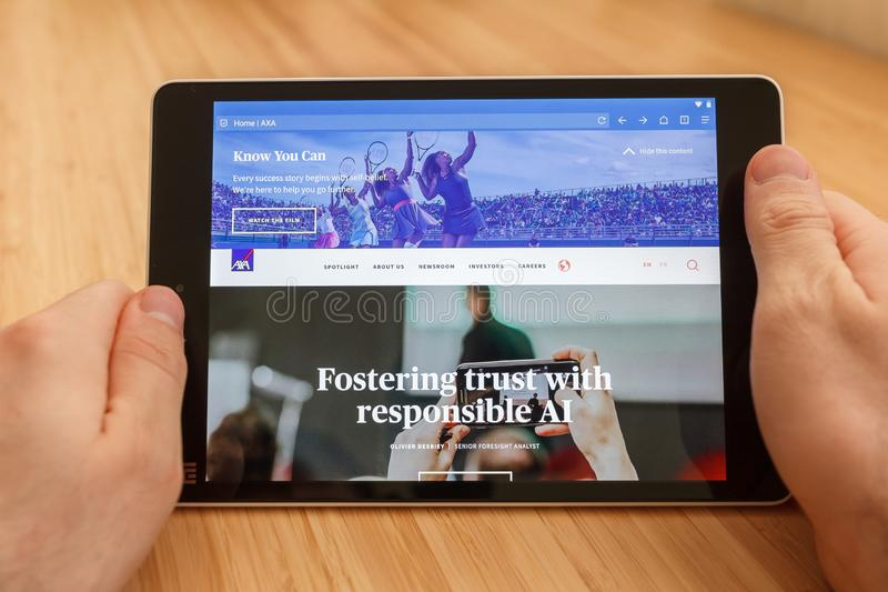 SAN FRANCISCO, US - 1 April 2019: Close up to hands holding tablet using internet and looking through AXA web site, in San. Francisco, California, USA. An stock photography