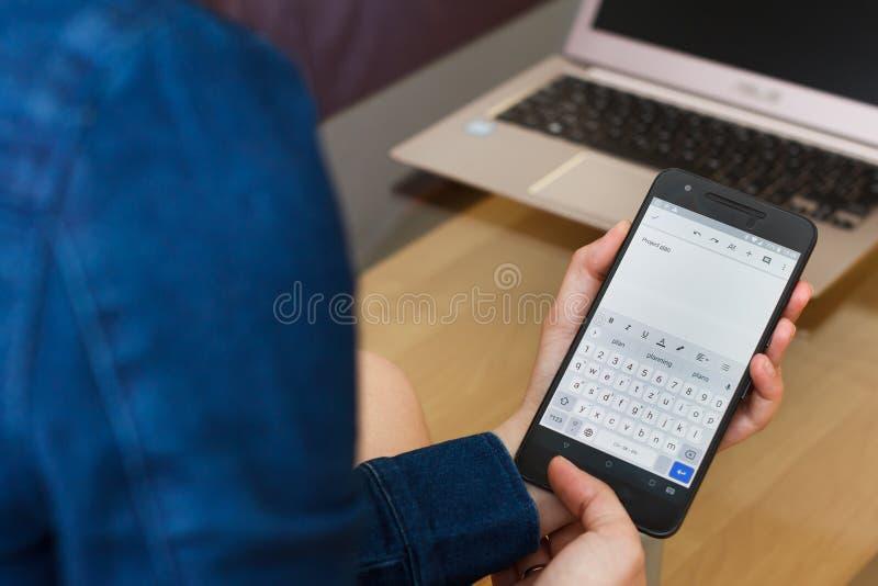 SAN FRANCISCO, USA - 22 avril 2019 : Fin jusqu'aux mains femelles tenant le smartphone créant le plan de projet par application d photos libres de droits