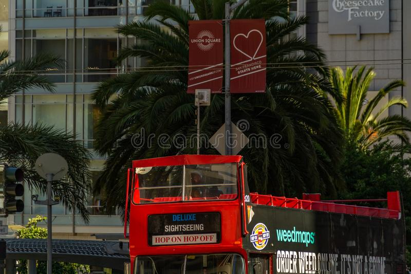 San Francisco, USA - July 17, 2019, a double-decker tourist bus, brightly painted in red, stands near the famous Union stock photo