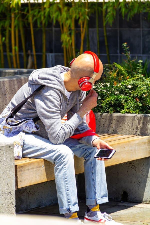 San Francisco, usa - Lipiec 12, 2019, młody elegancki łysy mężczyzna siedzi na ławce w ulicie w jaskrawych czerwonych hełmofonach fotografia stock