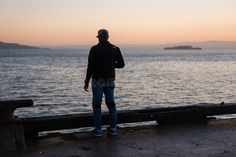 SAN FRANCISCO, USA - OCTOBER 12, 2018: Man fishing at sunrise with Alcatraz Island in the background stock photo