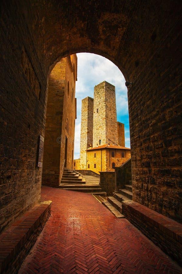 San Gimignano solnedgång från en tunnel, torn i squar centrala Erbe royaltyfria foton