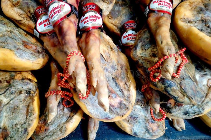 San Javier, Spagna - 29 luglio 2018: Intere gambe del prosciutto crudo da vendere in un supermercato spagnolo immagini stock