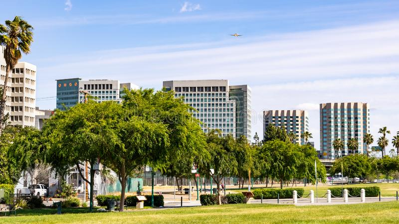 San Jose`s downtown skyline as seen from the shoreline of Guadalupe River Park on a sunny spring day; Silicon Valley, California stock images