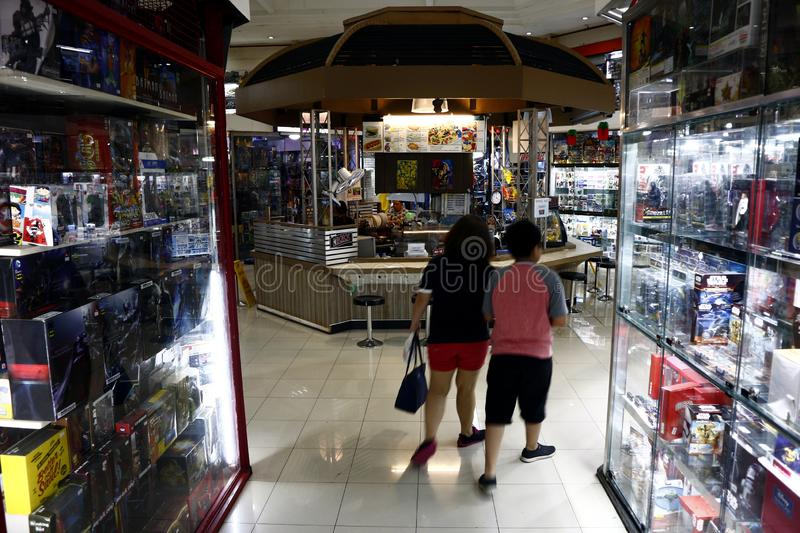 Customers pass by rows of toy stores and a snack bar inside a commercial shopping center. SAN JUAN, METRO MANILA, PHILIPPINES – AUGUST 21, 2019: Customers stock image