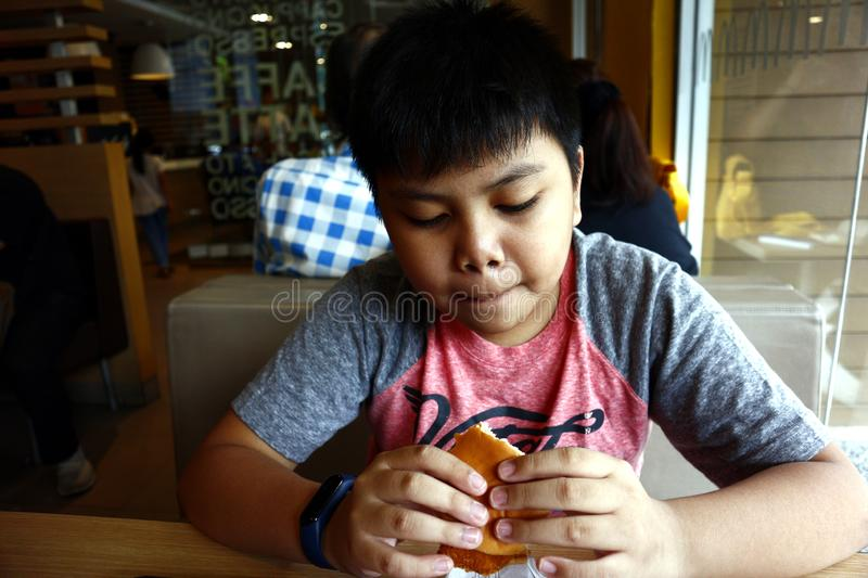 Young Asian boy eats a hamburger inside a fast food restaurant. SAN JUAN, METRO MANILA, PHILIPPINES – AUGUST 21, 2019: Young Asian boy eats a hamburger stock photography
