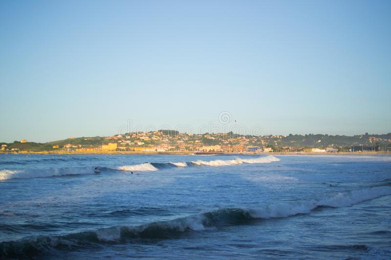 San Lorenzo beach and the Cantabrian Sea in Gijon, Asturias, Spain, with a green hill at the background.  stock photos