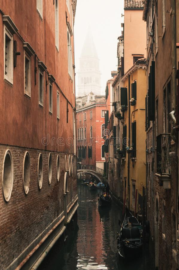 San Marco bell tower seen from an alley in Venice on a foggy day. In winter stock photos