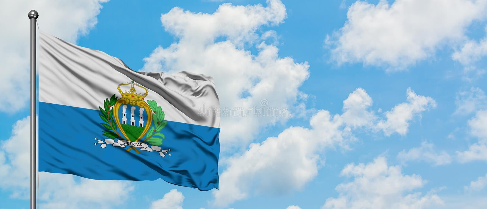 San Marino flag waving in the wind against white cloudy blue sky. Diplomacy concept, international relations.  royalty free stock photo