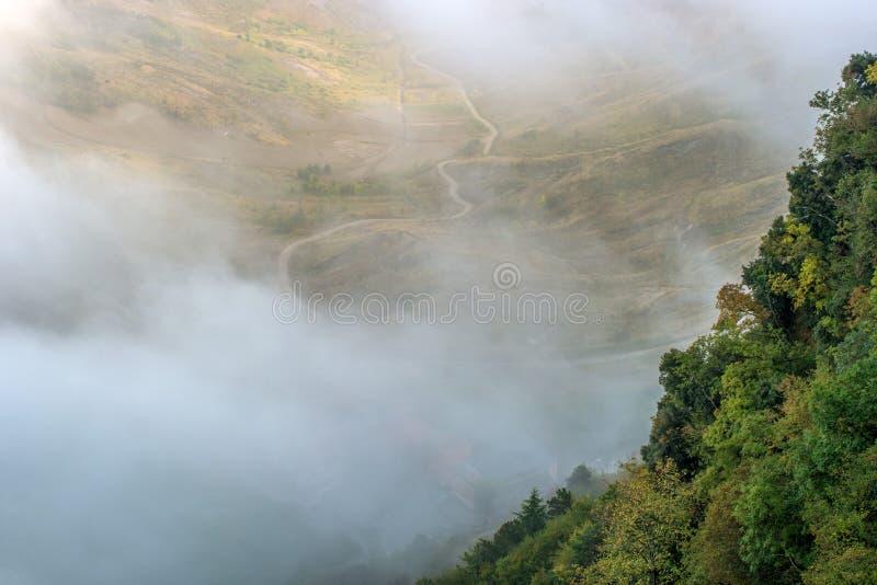 San Marino Italien Lutningen av berget som täckas med träd som döljas i mist arkivfoton
