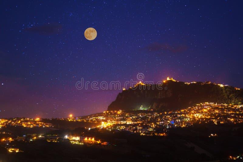 San Marino på fullmånenattfotoet med scenisk himmel och ljusa ljus av nattstaden fotografering för bildbyråer