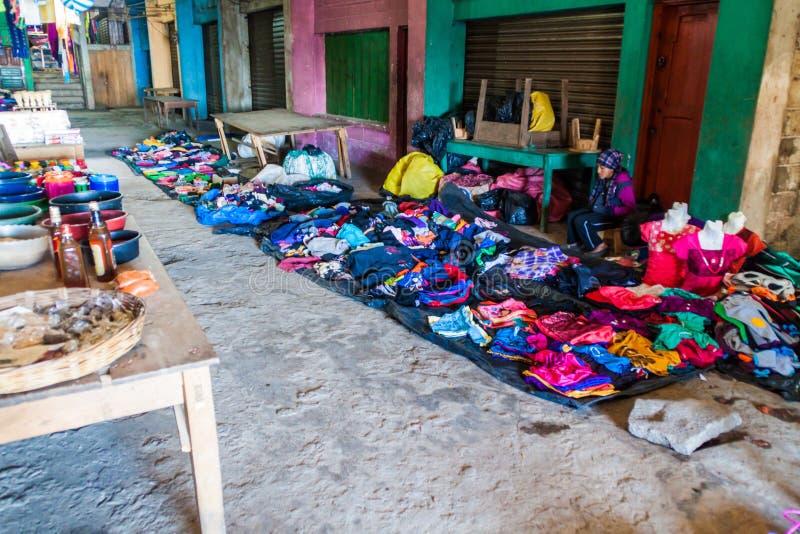 SAN MATEO IXTATAN, GUATEMALA, IL 19 MARZO 2016: I vestiti si bloccano su un mercato del villag di San Mateo Ixtatan immagine stock