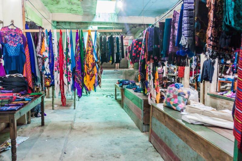 SAN MATEO IXTATAN, GUATEMALA, IL 19 MARZO 2016: Stalle dei vestiti su un mercato del villag di San Mateo Ixtatan immagini stock