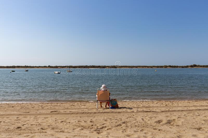 San Miguel beach in Cartaya, Huelva, Andalusia, Europe. Wooden planks path along the beach with tourists spending a sunny summer day on vacation with blue sky stock image