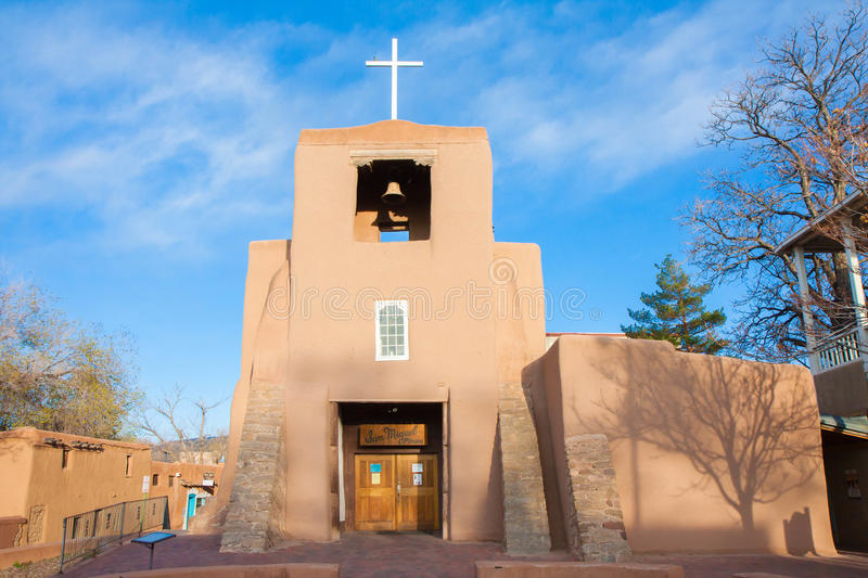 San Miguel Mission at sunset, Santa Fe, New Mexico. Horizontal shot, no people. Wispy clouds in background, blue sky, shadow of tree on building stock photo