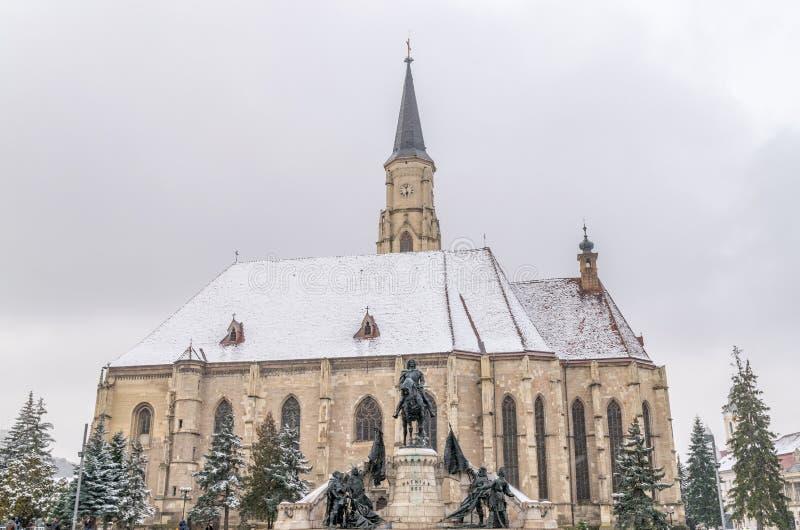 San Miguel y x27; iglesia y Matthias Corvinus Monument de s durante invierno en el centro de ciudad de Cluj-Napoca, Rumania fotos de archivo