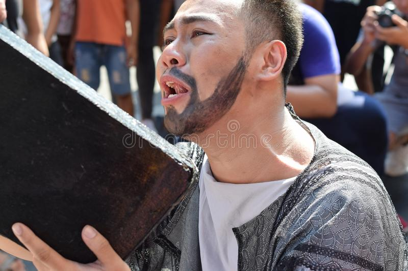 Real tears emit from the eyes of Judas Iscariot feeling pity to Jesus Christ, street drama, community celebrates Good Friday repr royalty free stock photography