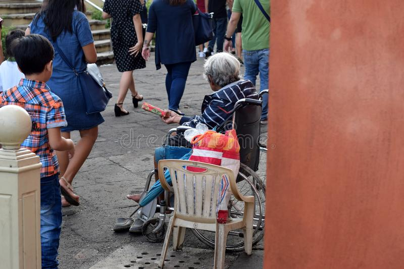 People pass by Ethnic old woman sitting on wheelchair holding Christmas gift box begging for alms at old church yard. San Pablo City, Laguna, Philippines royalty free stock photos