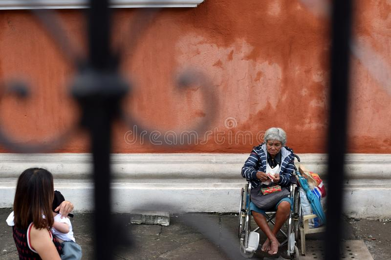 People pass by Ethnic old woman sitting on wheelchair holding Christmas gift box begging for alms at old church yard. San Pablo City, Laguna, Philippines royalty free stock photo