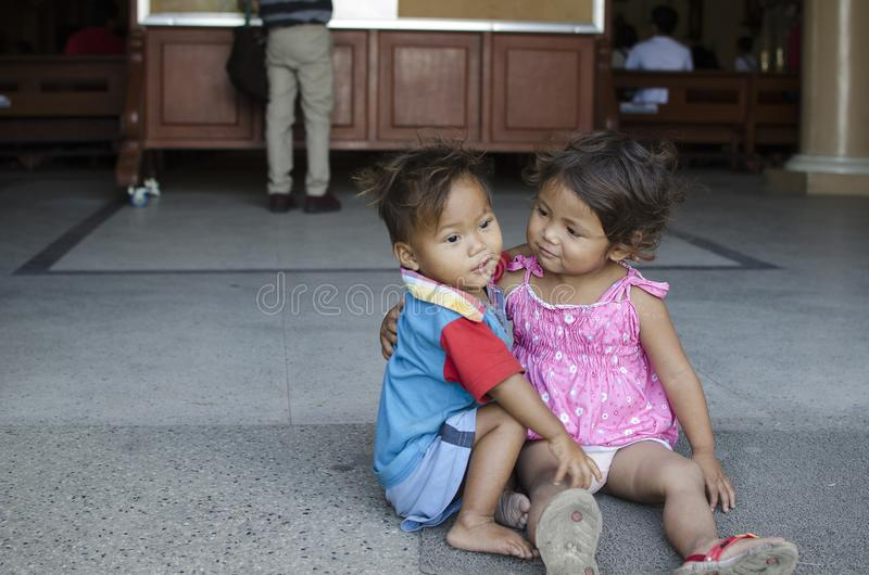 Homeless beggar`s children boy and girl, seated, take care of each other at church yard stock photography