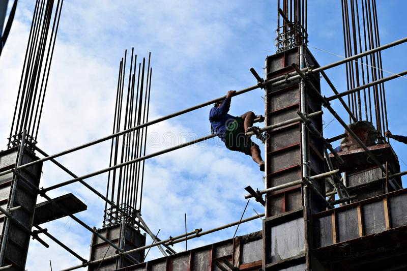 Filipino construction steel-man climbing down using scaffolding pipes on high-rise building. San Pablo City, Laguna, Philippines - June 20, 2018: Filipino stock photo