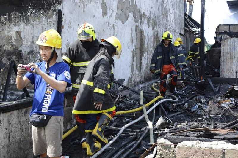 Local fireman taking photos of emergency response rescue during house fire that gutted interior shanty houses. San Pablo City, Laguna, Philippines - March 7 royalty free stock photo