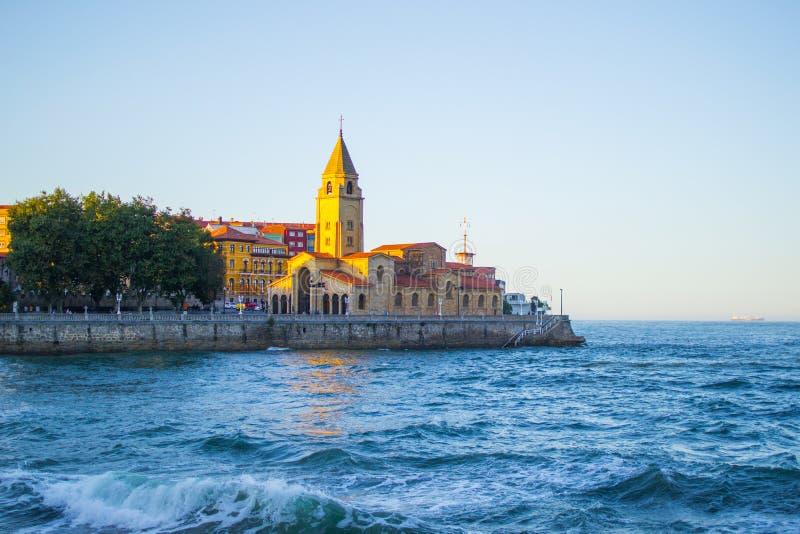 San Pedro`s Church Iglesia de San Pedro with the Cantabrian Sea in San Lorenzo beach, Gijon, Asturias Spain.  stock image