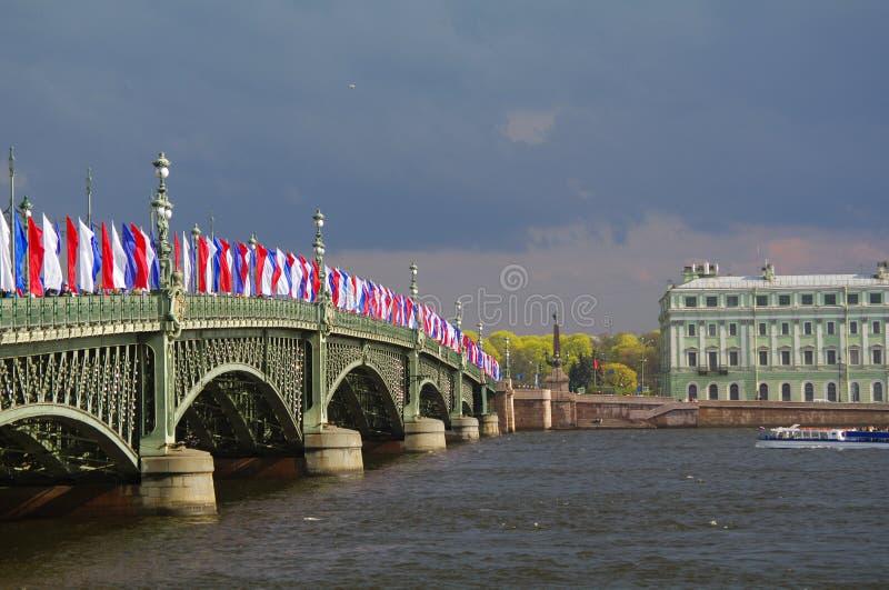 SAN PIETROBURGO, RUSSIA - MAY10, 2014: Ponte di Troitsky della trinità della basculla attraverso il fiume di Neva con le bandiere immagine stock