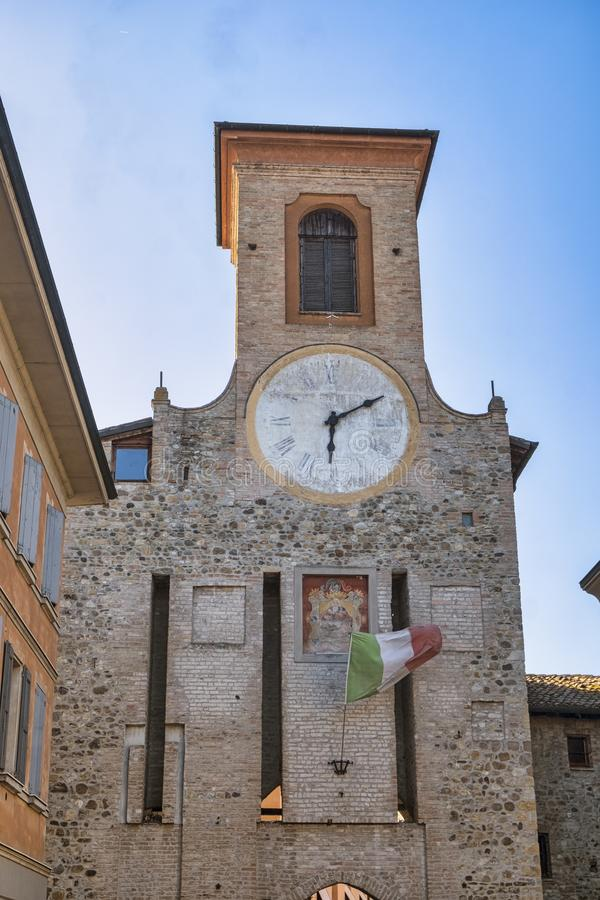 San Polo d`Enza Reggio Emilia: historic tower. San Polo d`Enza Reggio Emilia, Emilia-Romagna, italy: historic tower with clock and flag stock photos