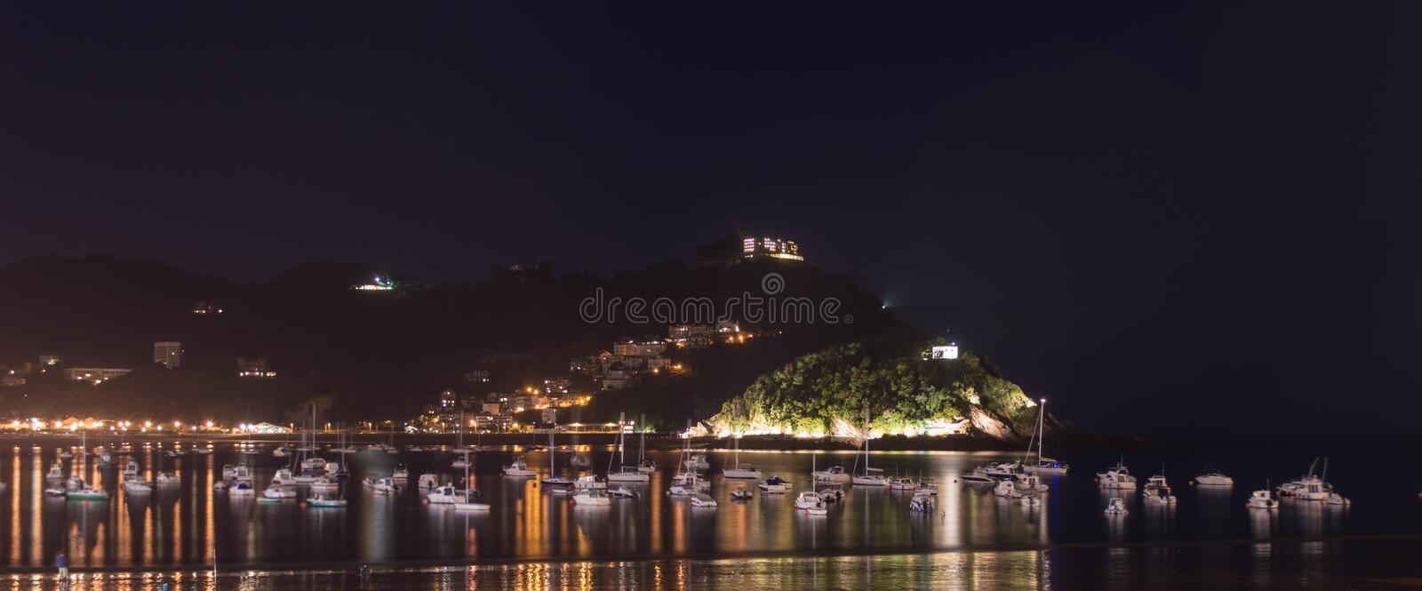 San Sebastian beach at night. Night on San Sebastian bay beach. Yacht and boat moored in the bay, light on the background royalty free stock images