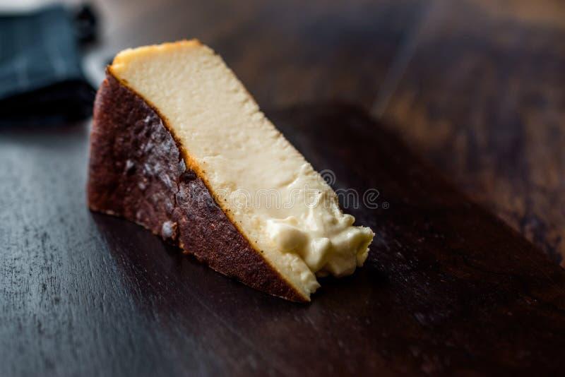 San Sebastian Cheesecake on wooden surface / Creamy Plain New York Style. Organic Dessert royalty free stock photography
