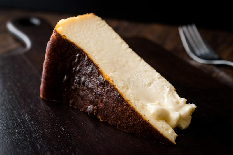 San Sebastian Cheesecake on wooden surface / Creamy Plain New York Style. Organic Dessert royalty free stock photos