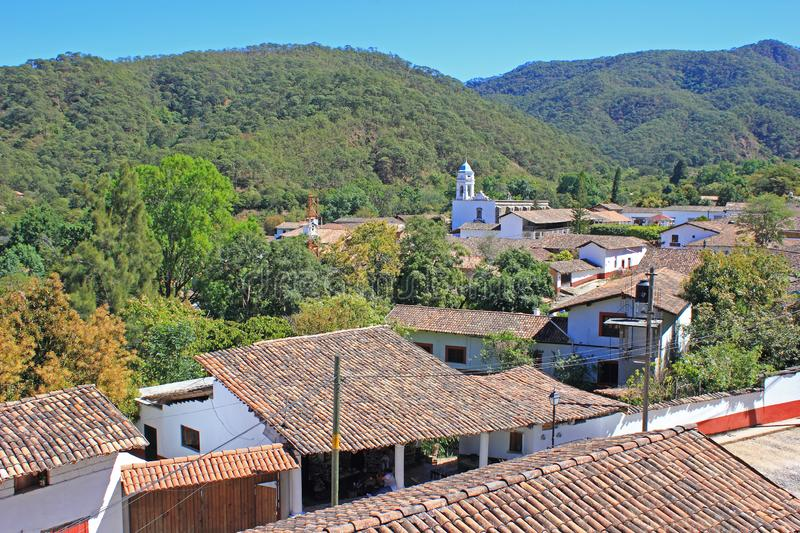 San Sebastian del Oeste, Jalisco, Mexico Cityscape. Brown brick roofs of historic houses in foreground, church and Sierra Madre mountains in background. San royalty free stock image