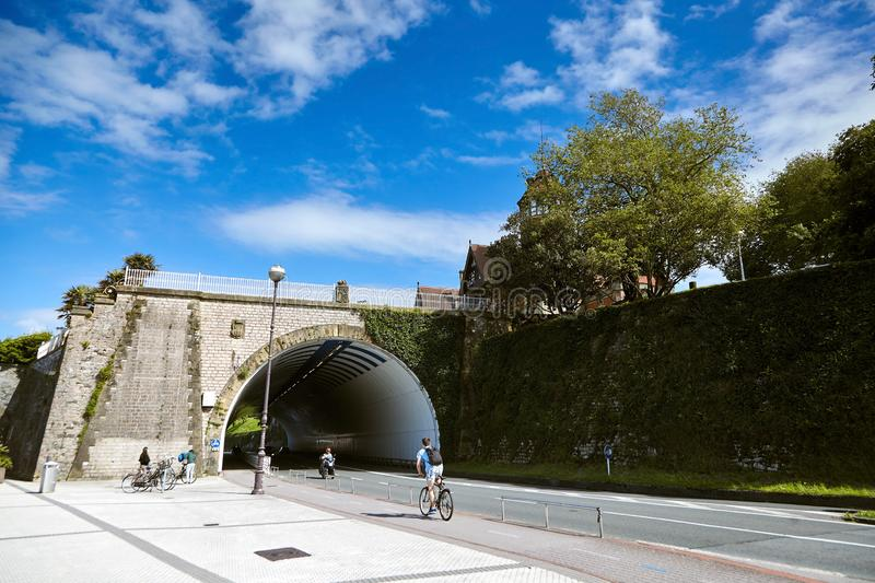 San Sebastian Donostia, Basque country, Spain: A young man on a bicycle rides under an stone bridge royalty free stock photos