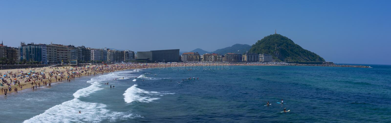 People bathing and sunbathing on Zurriola beach, city of San Sebastian royalty free stock images