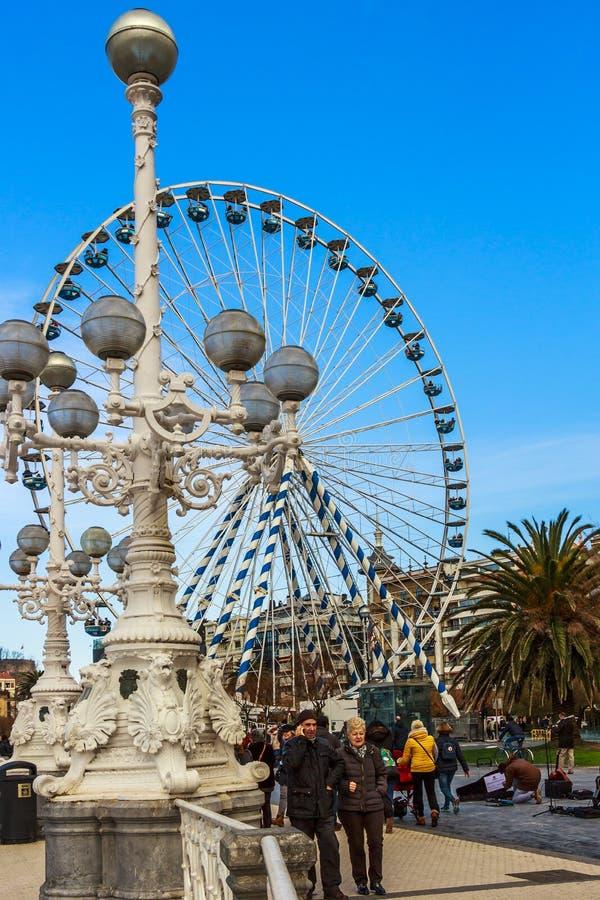 San Sebastian, Spain - Jan 2019: The promanade Paseo de la Concha along the La Concha beach of San Sebastian with ferris wheel. San Sebastian, Spain - Jan 2019 stock image