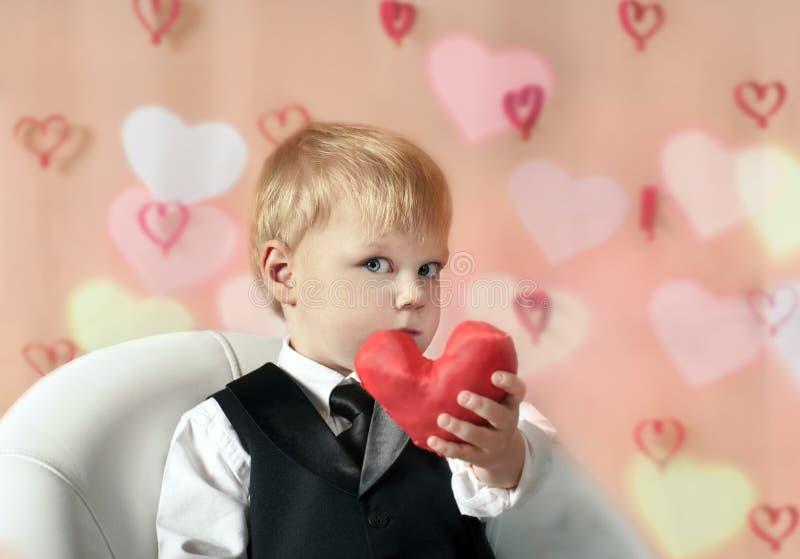 San Valentino - bambino sveglio con cuore rosso in mani. immagine stock