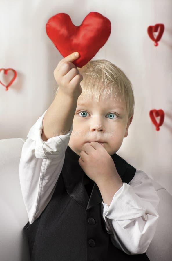 San Valentino - bambino sveglio con cuore rosso in mani. fotografie stock
