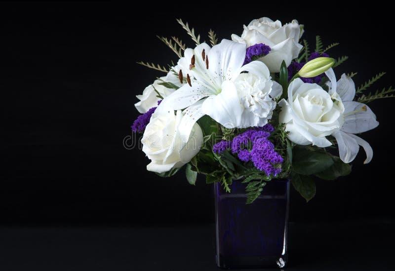 San Valentino Funerale Bouquet Viola fiori bianchi, Simpatia e condoglianze Concetto su sfondo nero fotografia stock libera da diritti