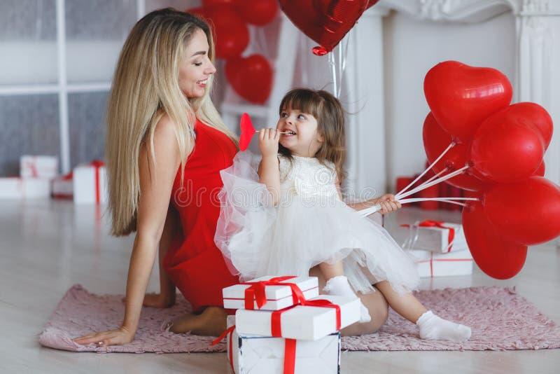 San Valentino - la giovane madre e la figlia in una stanza per terra con doni sullo sfondo di palloncini a forma di cuore rosso fotografie stock