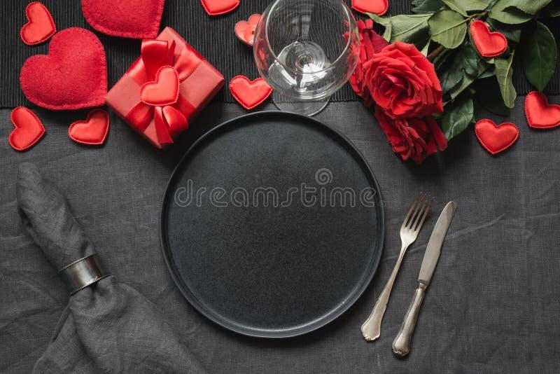 San Valentino o cena di compleanno Apposizione della tavola di eleganza con rosa rossa bouquet su tovaglia di biancheria nera immagine stock libera da diritti