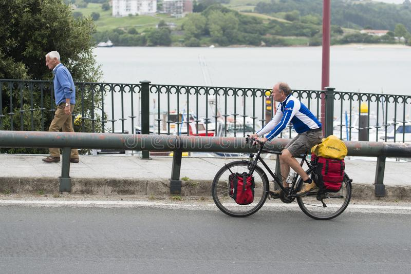 A tourist rides a bicycle laden with backpacks in Spain stock photo