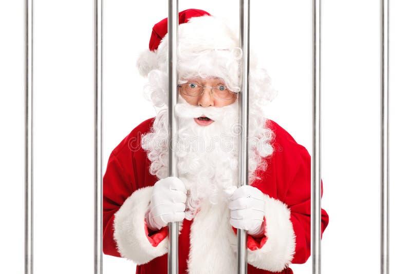 Sana Claus que se coloca detrás de barras en cárcel fotografía de archivo