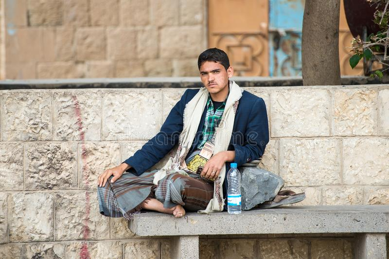 People in Sana'a, Yemen. SANA'A, YEMEN - JAN 11, 2014: Unidentified Yemeni man sits in the street in Sana'a. People of Yemen suffer of poverty due to the royalty free stock photos