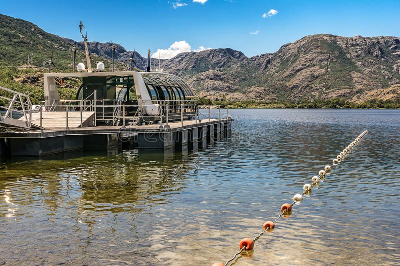 Self-sufficient boat moved with wind and solar energy without fossil fuel in the Sanabria lake in Zamora Spain. The Sanabria lake is the largest lake in Spain of stock photography