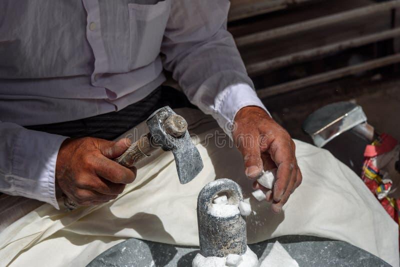 Iranian man crashing sugar cones for sale in bazaar. Sanandaj. Kurdistan Province. Iran royalty free stock photos