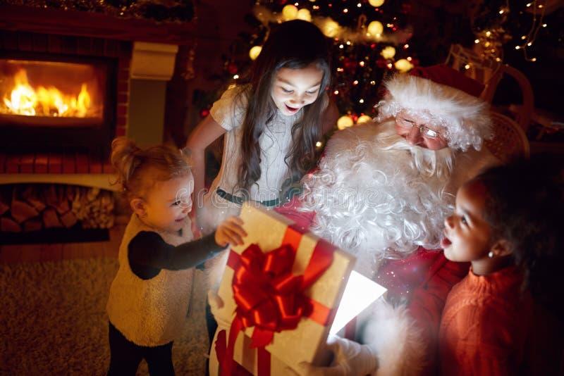 Sanat Claus et trois petites filles ouvrant Noël magique g images libres de droits