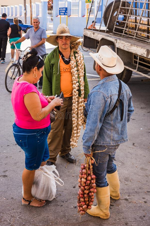 Cuban Garlic Seller. Sancti Spiritus , Cuba / March 15, 2017: Cuban women buys braids of fresh garlic from street sellers dressed like cowboys stock photos