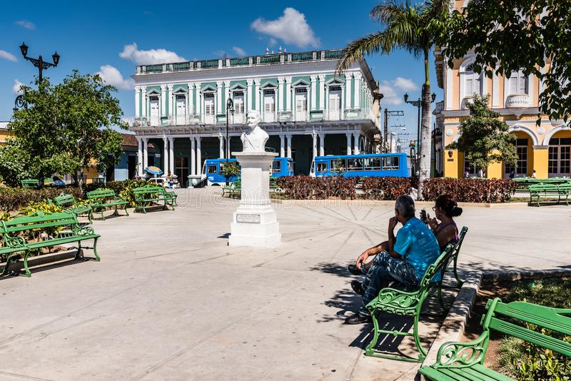 Parque Serafin Sanchez. Sancti Spiritus , Cuba / March 15, 2017: Traditional Spanish park with green benches and white stone monument stock image