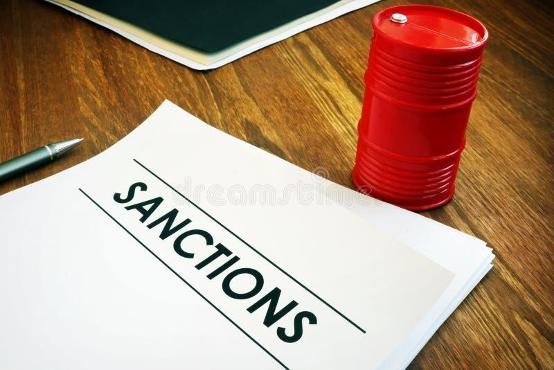 Sanctions list with model of oil barrel. Sanctions list with model of red oil barrel stock image